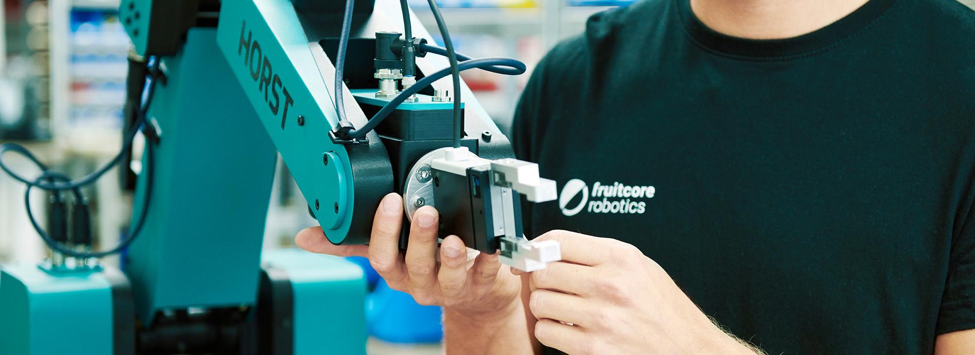 Junger Mann greift an den Roboterarm